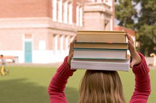 Girl balancing books on her headの写真素材 [FYI01989217]