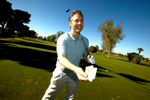 Man holding tee card on golf courseの写真素材 [FYI01989258]