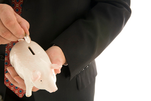 Man putting coin in piggy bankの写真素材 [FYI01989281]
