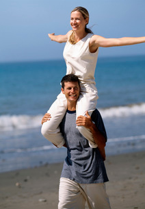 Man carrying wife on shoulders at beachの写真素材 [FYI01989300]