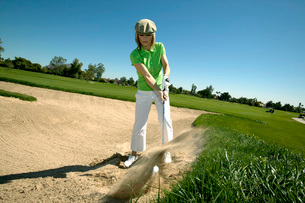 Woman hitting golf ball out of bunkerの写真素材 [FYI01989336]