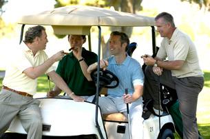 Men relaxing with cigars in golf cartの写真素材 [FYI01989374]