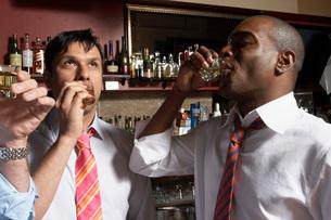 Businessmen having shots in barの写真素材 [FYI01989399]