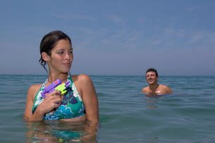 Couple playing with squirt guns in oceanの写真素材 [FYI01989423]