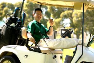 man relaxing with cigar in golf cartの写真素材 [FYI01989469]