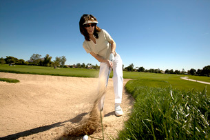Woman hitting golf ball out of bunkerの写真素材 [FYI01989471]