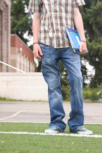 Teenage school boy carrying school booksの写真素材 [FYI01989487]