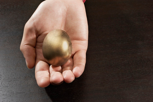 Hand holding golden eggの写真素材 [FYI01989512]