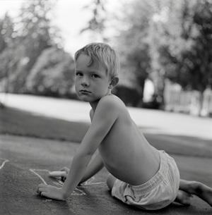 Young boy drawing with sidewalk chalkの写真素材 [FYI01989546]