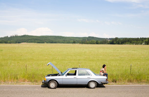 Woman sitting on trunk of broken carの写真素材 [FYI01989547]