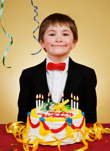 Boy smiling beside his birthday cakeの写真素材 [FYI01989594]