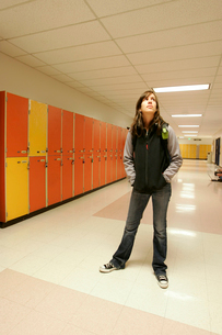 Teenage girl standing in school hallwayの写真素材 [FYI01989600]