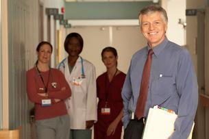 doctor standing in corridor with peopleの写真素材 [FYI01989645]