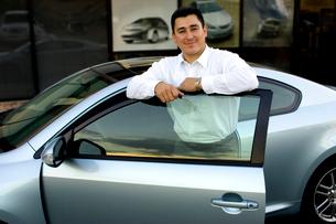 Hispanic man with new carの写真素材 [FYI01989701]