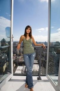 Young woman standing on balconyの写真素材 [FYI01989724]