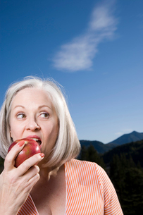 Mature woman eating appleの写真素材 [FYI01989743]