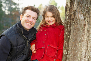 Father and daughter smile by tree trunkの写真素材 [FYI01989747]