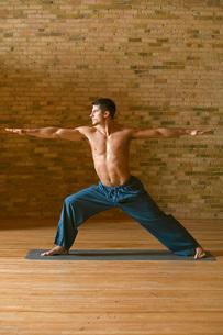 Young man practicing yoga indoorsの写真素材 [FYI01989788]