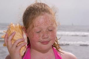 Young girl listening to seashellの写真素材 [FYI01989821]