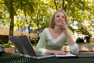 Woman using a laptop outdoorsの写真素材 [FYI01989854]