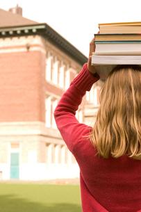 Girl balancing books on her headの写真素材 [FYI01989882]