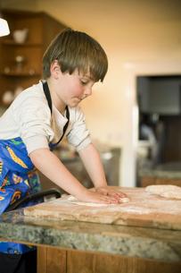 Boy kneading dough on wooden boardの写真素材 [FYI01989902]