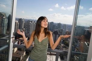 Young woman standing on balconyの写真素材 [FYI01989903]