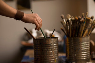 Man dipping into bucket of paintbrushesの写真素材 [FYI01989923]
