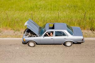 Woman in broken down carの写真素材 [FYI01989956]