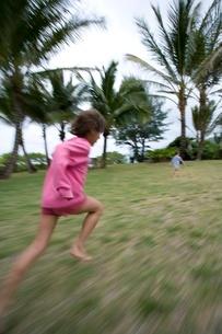 Two children running in grass in Hawaiiの写真素材 [FYI01990016]