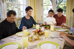 Family saying prayer at dinner tableの写真素材 [FYI01990030]