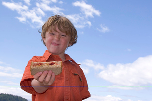 Young boy holding out sandwichの写真素材 [FYI01990038]