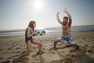 Couple playing  with watergun at beachの写真素材 [FYI01990104]