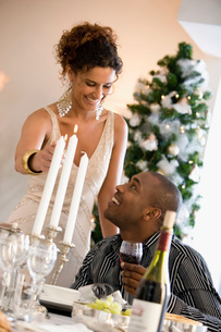 Woman lighting candles at dinner tableの写真素材 [FYI01990118]