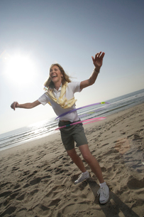 Woman with hula hoops on the beachの写真素材 [FYI01990192]