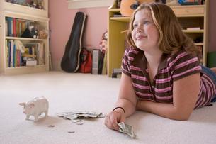Girl on floor with her piggy bankの写真素材 [FYI01990206]