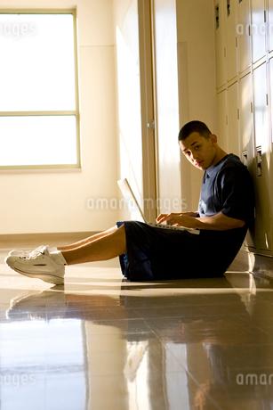 Boy in school hallway with laptopの写真素材 [FYI01990207]
