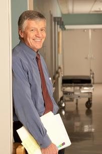 Male doctor standing in corridorの写真素材 [FYI01990292]