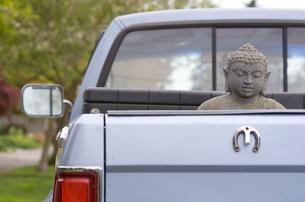 Buddha statue in back of pickup truckの写真素材 [FYI01990313]
