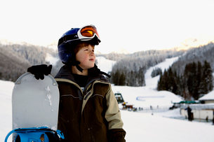 Boy holding snowboard on slopesの写真素材 [FYI01990335]