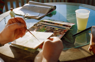 person's hands painting with watercolorsの写真素材 [FYI01990358]