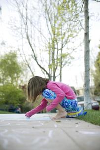 Girl making chalk drawings on sidewalkの写真素材 [FYI01990371]