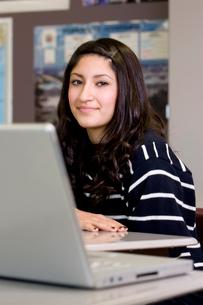 Teenage girl in classroom with laptopの写真素材 [FYI01990401]