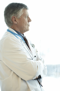 Male doctor looking out hospital windowの写真素材 [FYI01990433]