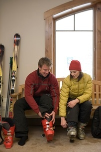 Couple removing their ski bootsの写真素材 [FYI01990436]