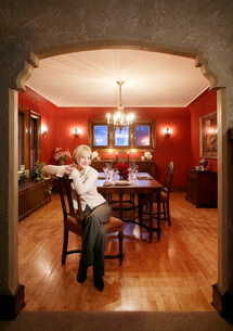 Woman sitting in dining roomの写真素材 [FYI01990453]