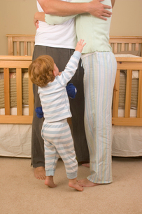 Child reaching up to hugging parentsの写真素材 [FYI01990492]