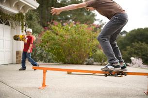 Boy playing on skateboard in drivewayの写真素材 [FYI01990500]