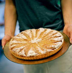Pastry chef hold tart on stone cookwareの写真素材 [FYI01990523]