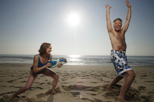 Couple playing  with watergun at beachの写真素材 [FYI01990534]
